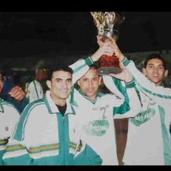 Nashat Akram lifts the Umm Al Ma'arak Cup in 2002 with his teammates