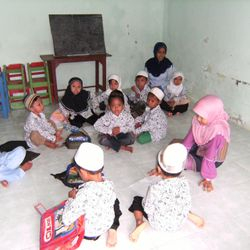 Students in their classroom but on the floor due to shortage of tables & chairs.