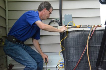 Experienced technician repairing air conditioning unit.