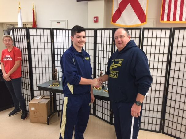 Cadet Ben Davis is congratulated by match coordinator for placing 2nd  overall individually, in the precision rifle class in Anniston, AL, hosted by Jefferson County High School Saturday, 10 Dec.